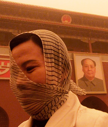 A WOMAN COVERS HER HEAD WITH A SCARF TO PROTECT HERSELF IN A SAND STORM IN BEIJING