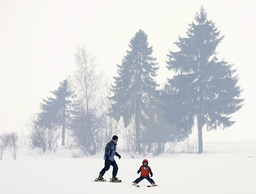 Polish man with a child enjoy skiing during the first spring day in the southern mountain town of Nowy Targ