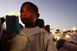 AN EAST TIMORESE BOY HOLDS A CANDLE DURING A MASS PRAYER SERVICE IN TACITOLU