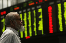 Stockbroker looks at electronic board during trading session inside trading hall of Karachi Stock Exchange