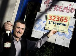 Lottery salesman Avelino Rueda takes a drink of Cava outside his lottery shop in Madrid