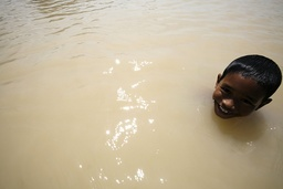 Boy poses as he sits in flood outside his residence in Malaysia's village of Parit Sidang Seman Benteng