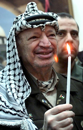 PALESTINIAN PRESIDENT YASSER ARAFAT LIGHTS A CANDLE DURING A CHRISTMAS CEREMONY AT HIS OFFICE IN THE WEST BANK CITY OF RAMALLAH