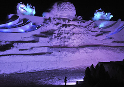 A visitor stands in front of a giant Santa Claus ice sculpture for the upcoming 25th Harbin International Ice and Snow Festival at a park in Harbin