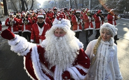 Procession of men dressed as Santa Claus walks through centre of Bishkek during annual parade