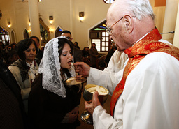 A priest gives holy communion to a resident during Christmas mass at Virgin Mary church in Baghdad