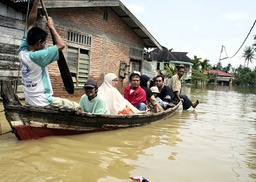 Villagers travel in a boat through floodwaters in the village of Pelawi