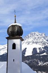 Church tower with onion dome at Ellmau ski resort, Wilder Kaiser mountains beyond, Tirol, Austria, 2009