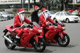 Men dressed as Santa Claus ride motorcycles at main street in Jakarta