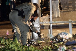 Policemen inspect the crime scene of a bomb blast at the Victory Monument during the evening of New Year's eve in Bangkok