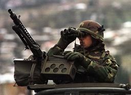 A NATO SOLDIER LOOKS THROUGH BINOCULARS