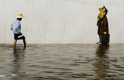 A THAI WOMEN WALKS THROUGH FLOODED STREETS IN THE RESORT TOWN OF HUA HIN