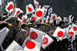 Well-wishers wave Japanese national flags as Japan's Emperor Akihito makes a public appearace to celebrate his 73rd birthday at the Imperial Palace in Tokyo