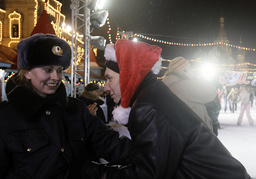 A police officer smiles as people celebrate New Year's Day on an ice rink in Red Square in Moscow