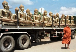 A BUDDHIST MONK LOOKS AT BUDDHA IMAGES TO BE TRANSPORTED TO CAMBODIA