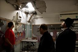 Israelis look at a classroom damaged after a rocket landed in Beersheba