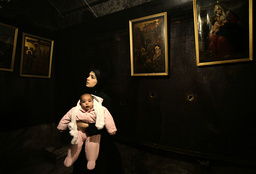 Palestinian woman holds daughter in grotto in Bethlehem