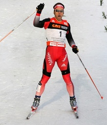 Switzerland's Eigenmann celebrates as he crosses the finish line to win the first of four 'Tour de Ski' Cross Country World Cup competitions in Munich's Olympic stadium