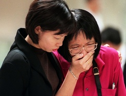 AN OFFICIAL COMFORTS A RELATIVE AT SINGAPORE AIRPORT