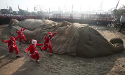 Children dressed as Santa Claus run near sand sculpture of Santa Claus during Christmas celebrations in Chandigarh