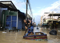 A boy use a makeshift raft to travel through the flooded streets in Had Yai district of Songkhla province