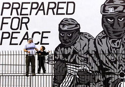 A MAN AND BOY STAND ON A FENCE BY A PROTESTANT MURAL IN NORTH BELFAST