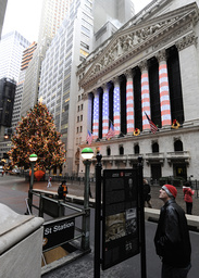 A tourist reads a historical marker outside the New York Stock Exchange shortly after the exchange opened for business on the last day of the year