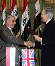 Iraqi Defence Minister Jassim shakes hands with British Ambassador to Iraq Prentice after signing an agreement in Baghdad