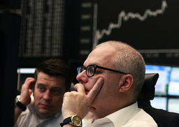 Traders check their monitors in front of the German DAX Index board at Frankfurt's stock exchange in Frankfurt