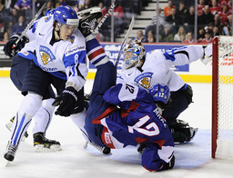 Slovakia's Mraz is thrown to the ice by Finland's Hovinen during the first period of play at the 2012 IIHF U20 World Junior Hockey Championship in Calgary