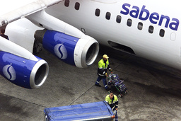 A WORKER AT BELGIAN AIRLINE SABENA PUSHES A BABY BUGGY BY PARKED ON THE TARMAC AT BRUSSELS' ZAVENTEM AIRPORT