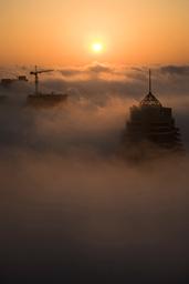 Low level clouds float over Dubai's Marina area as the sun sets on Dubai on New Year's Eve