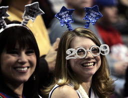 Two women wear 2009 Happy New Year decorations as they watch the NBA game between the Detroit Pistons and the New Jersey Nets in Auburn Hills, Michigan
