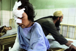 INJURED AFGHAN REFUGEE MOTHER ZARI GUL IS ASSISTED BY HER BROTHER AT THE AL-KHIDMAT AFGHAN REFUGEE HOSPITAL IN QUETTA