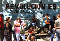 People wait for transportation near a graffiti reading Revolution is: never lie, never violate ethic principals in Santiago de Cuba