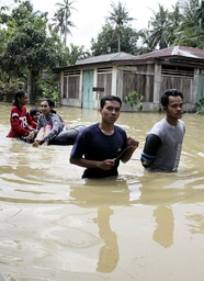Villagers walk through floodwaters in the village of Pelawi in the district of Langkat