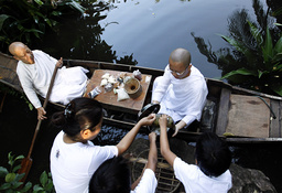 Buddhist nuns receive food from people as they sit in a boat on floodwaters at the Sathira-Dhammasathan Buddhist meditation centre in Bangkok