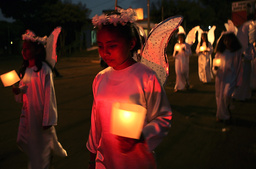 Children dressed as angels take part in a Christmas Festival in the streets of Managua