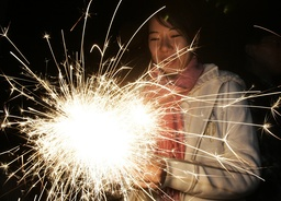 A women plays with sparklers to celebrate New Year in Taipei