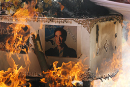 Supporters of Thailand's ousted PM Thaksin set fire to a coffin with a picture of new PM Abhisit stuck on it in Udon Thani province