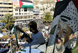 A PALESTINIAN GUNMAN WATCHES OVER FATAH RALLY IN NABLUS