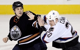 Oilers' Jacques and Canucks' Cowan fight during NHL action in Edmonton
