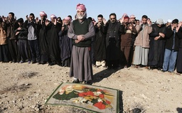 Residents pray in front of a picture showing former Iraqi President Saddam Hussein and a map of Iraq in Tikrit