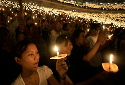 Christians hold candles during Christmas mass in Jakarta