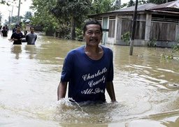 Villagers walk through floodwaters in the village of Pelawi