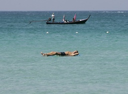 A tourist relaxes at the sea at Patong beach in Phuket province