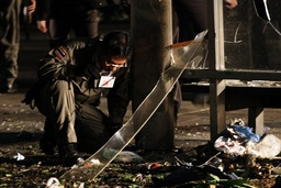 A policeman inspects the crime scene of a bomb blast at the Victory Monument during the evening of New Year's Eve in Bangkok