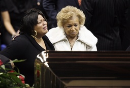 Family member of James Brown weeps while looking at his coffin during a public viewing and funeral for the legendary singer in Augusta