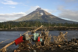 Villager dries clothes on a fallen tree trunk after typhoon Durian in central Philippines