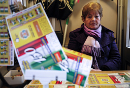 A national lottery ticket vendor poses while selling a stack of tickets in downtown Rome